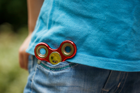 Fidget hand spinner in blue jeans pocket background. Trendy and popular toy for children and adult