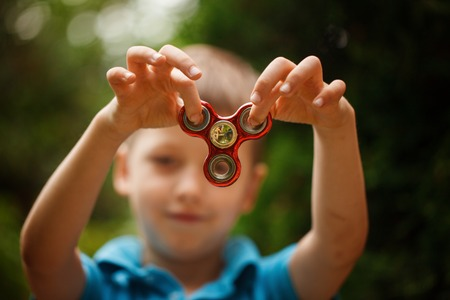 Cute little boy playing with fidget hand spinner in summer day. Popular and trendy toy for children and adult. Stock Photo