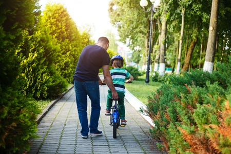 teaches: Dad teaches his son riding on bicycle in summer park. Back view.