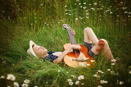 ballad: Teenage boy lying on grass with his acoustic guitar.