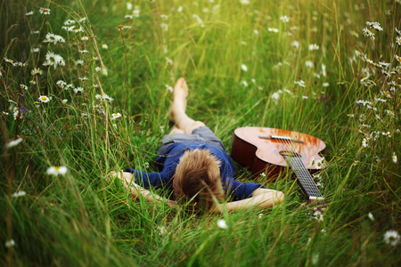 Teenage boy lying on grass with his acoustic guitar.