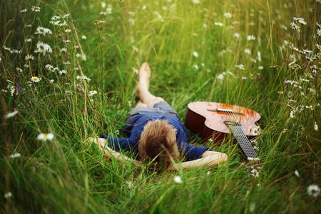 Nastoletni chłopak leżący na trawie z gitarą akustyczną.