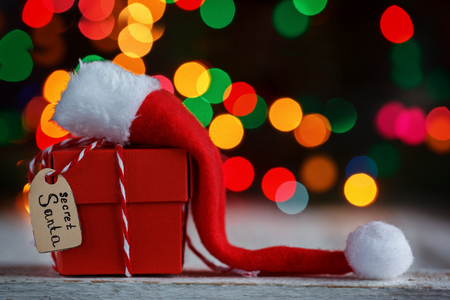 Christmas present or box for secret santa with Santa hat on colorful bokeh background. Фото со стока - 89710068