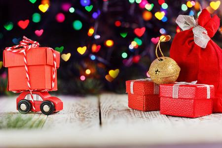 Miniature voiture rouge portant une grosse boîte rouge sur fond de bokeh coloré et aller derrière les vacances de noël de vacances notion Banque d'images - 90215798