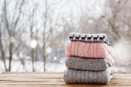 Stack of knitted sweaters on wooden tableon winter nature background. Stock Photo