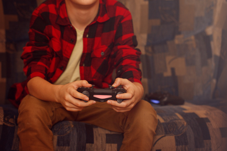 Young boy holding game controller playing video games.