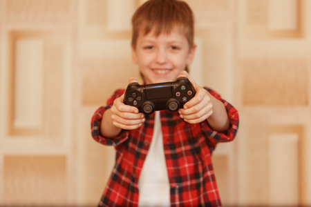 Young boy holding game controller playing video games