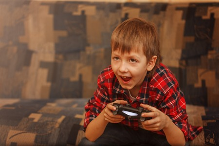 Young boy holding gamepad and playing video games.