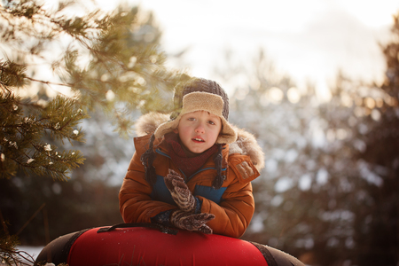 Cute boy holding a tubing in snowy winter day Stock Photo