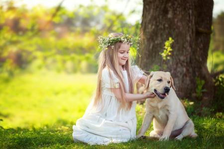 Cute little girl hugs a big dog in summer park.