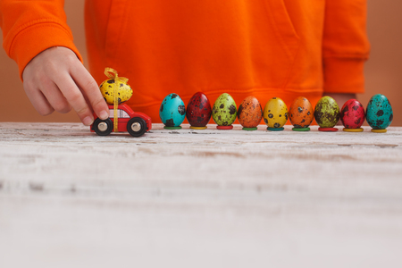 Child hands playing easter egg on car on orange background. Holiday concept. Stock Photo