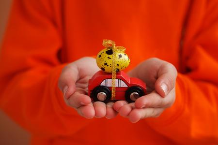Child hands holding easter egg on car on orange background. Holiday concept.