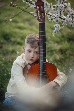 Portrait boy with guitar sitting on the grass in summer day