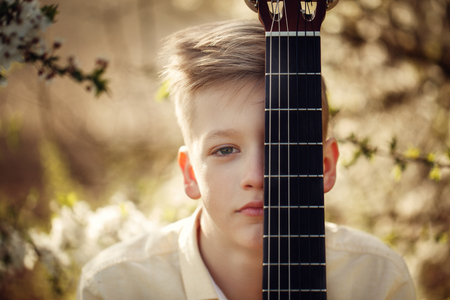 Closeup Portrait boy with guitar in summer day