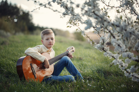 Cute boy making music playing the guitar on nature Stock fotó