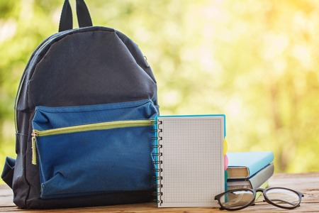 School backpack with books on wooden table and nature background.