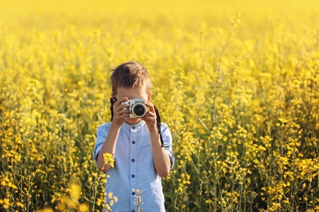 Portrait of little boy photographer with camera on sunset yellow field background.