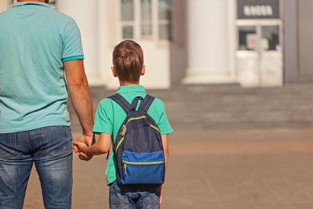 Ragazzino sveglio con lo zaino che va a scuola con suo padre. Vista posteriore