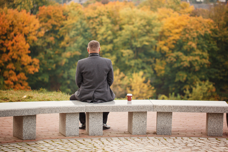 Lone man sitting on the stone bench and looking at nature. Back view.