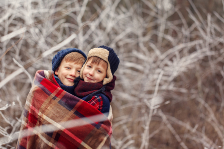 Two little boys friends hug under warm blanket in winter forest. . Brother love. Concept friendship.