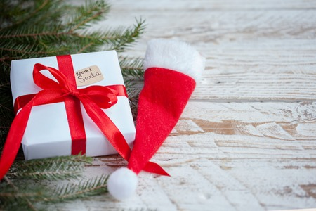 Christmas white box or present with red ribbon for secret santa with santa hat on wooden table Stock Photo
