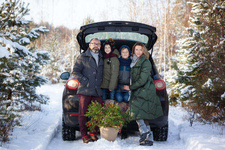 Happy family in black car at snowly winter day.