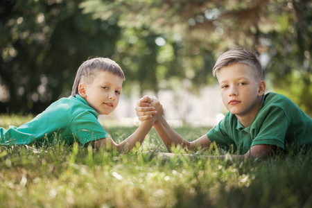 Two boys clasped hands engaged in an arm wrestle on green lawn in summer day. 写真素材