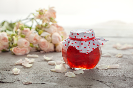 Homemade jam of rose petals on a table with bouquet of roses.
