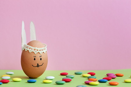Cute handmade egg bunny on pink background with colored candies. Happy Easter concept Stockfoto