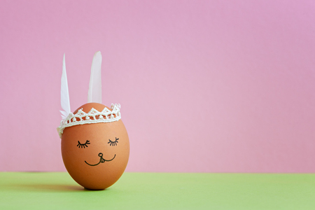 Cute handmade egg bunny on pink background. Happy Easter concept