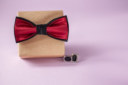 One gift box wrapped in craft paper and tied with the bow tie on purple background. Concept Father's Day or Birthday card.