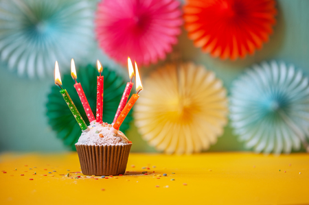 Birthday celebration with cupcake and colorful candles. Happy Birthday concept.