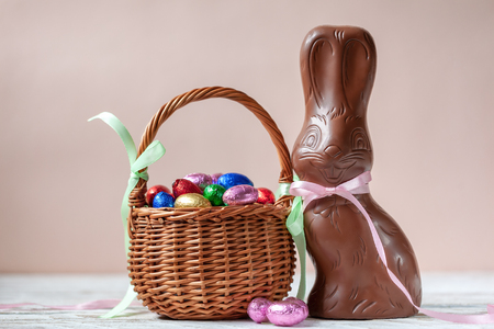 Delicious chocolate easter bunny and sweets on pink background, easter concept background.