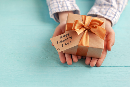 Kid's hands holding gift box wrapped in craft paper and tied with bow. Concept Father's Day or Birthday background.