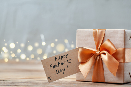 Happy Father Day greeting card with tag on wooden background. Holiday present concept.