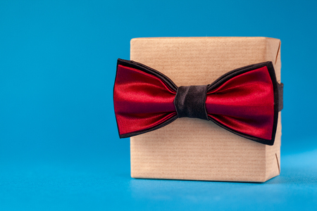 Happy Father Day greeting cardpaper and tied with the bow tie on blue background.