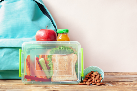 School lunch box with sandwich, vegetables, juice and almonds on table. Healthy eating habits concept.
