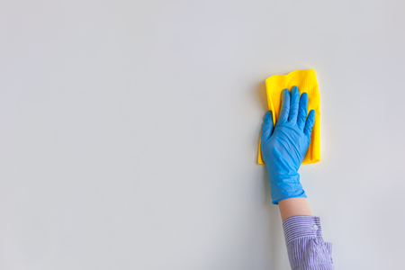 Employee hand in blue rubber protective glove wiping wall from dust with dry rag. General or regular cleanup. Commercial cleaning company. Copy space.