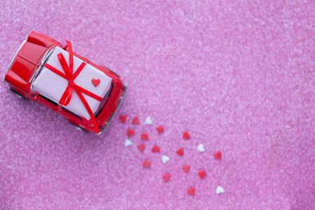 Red toy car delivering carrying on roof gift box with small red hearts on pink background. Valentine's day concept.