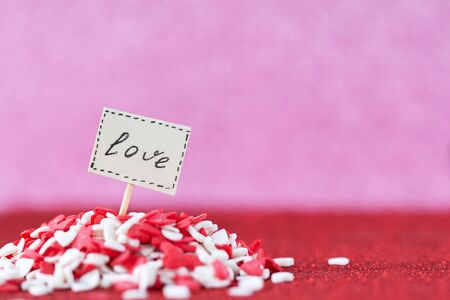 Valentine day concept. Love text composed on board in heap red and white hearts on pink background.