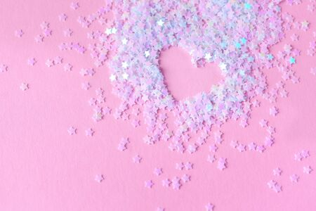Heart made of white stars confetti on pink background. Love concept. Heart with sparkles.