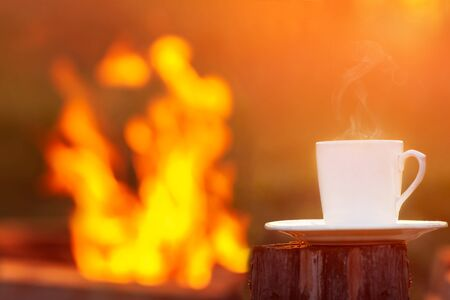 White cup of coffee or tea on sunset and bonfire background. Leisure time and chill out concept.