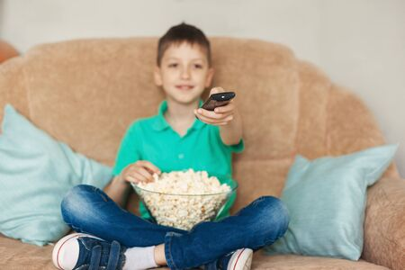 Child watching tv, relaxes and eating popcorn on sofa in his room. Focus on a hand with a TV remote control. Zdjęcie Seryjne