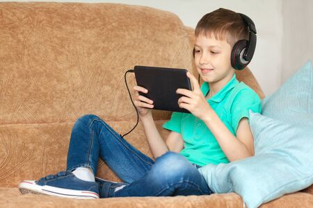 Child boy using digital tablet and headphones on sofa in living room. Kid studying from home and playing with gadget
