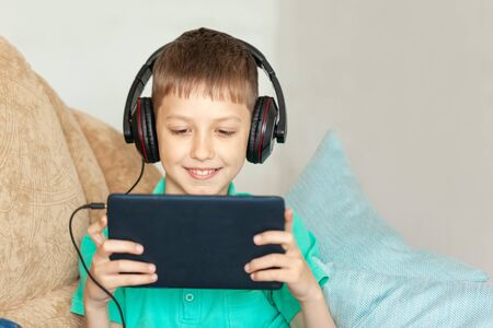 Child boy using digital tablet and headphones. Kid studying from home and playing video game with gadget Stock Photo
