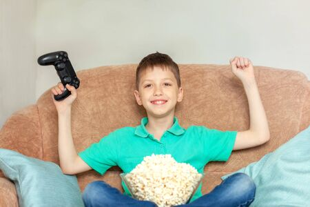 Child playing online video games and eating popcorn sitting on sofa in living room at home. Gaming video games concept Zdjęcie Seryjne