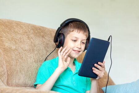 Child boy using digital tablet, headphones and makes video call on sofa in living room. Zdjęcie Seryjne
