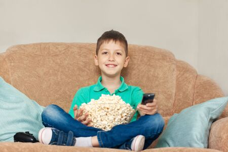 Child watching tv, relaxes and eating popcorn on sofa in his room.
