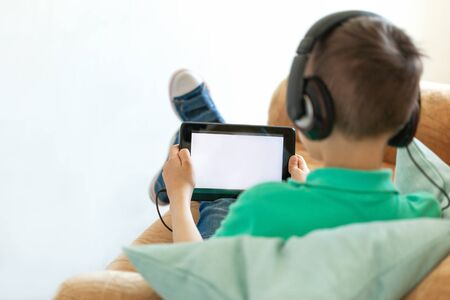 Child boy using digital tablet and headphones with white blank screenon sofa in living room. Zdjęcie Seryjne