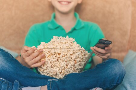 Child watching tv, relaxes and eating popcorn on sofa in his room. Close-up on a plate with popcorn and a hand with a TV remote control.